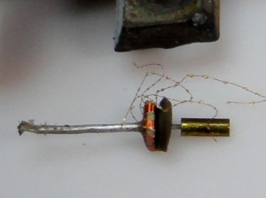 Piano wire holding the damper, the coil former and the cantilever assembly.